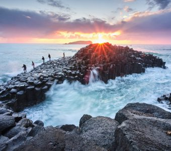 Fisherman on Giants Causeway at sunrise with red ball of the sun and nice clouds